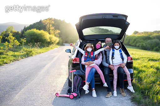 Family with two small daughters on trip outdoors in nature, wearing face masks.
