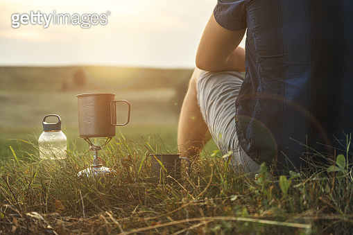 Adventure, travel, tourism and camping concept. Tourist drinking tea from a mug in the camp.
