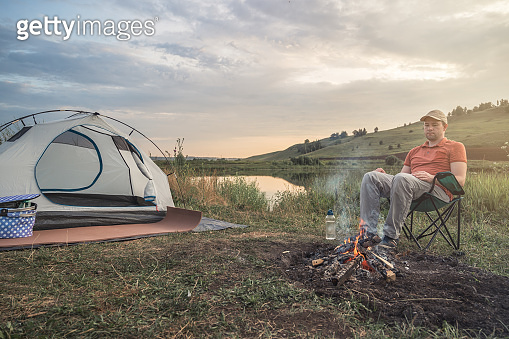 Young man sits on chair near fire and tent against the backdrop of nature and the lake.
