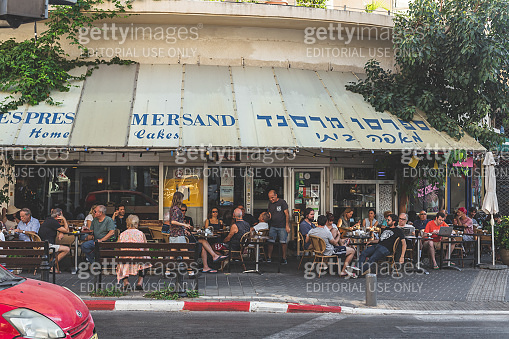 People in an outdoor sitting area of the Mersand cafe in Tel Aviv