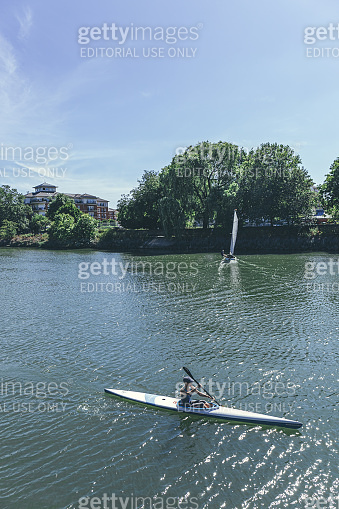 A woman is kayaking and a man is sailing on the River Thames in London