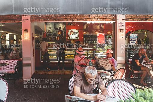 People sitting on an outdoor terrace of the Segafredo Zanetti Espresso cafe on Dizengoff Street in Tel Aviv, Israel