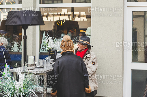 People socializing and drinking coffee in a cafe outdoor area on Market Place in Bad Kissingen, Germany