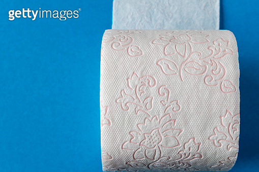Toilet paper roll on a blue background. Close up.