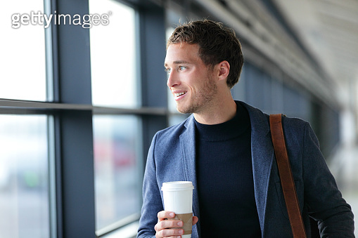 Happy businessman going to work drinking coffee - travel lifestyle or morning commute urban living. Young professional man near window in office builing or at airport terminal business class flight.