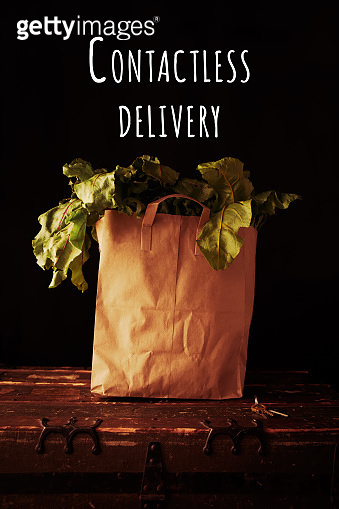 Paper bag with beet greens, with Contactless delivery wording. Concept of healthy grocery shopping