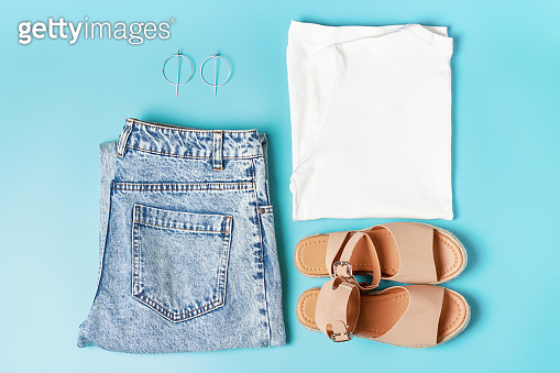Set of women's fashion clothes for the summer. Jeans, white shirt and sandals on blue background