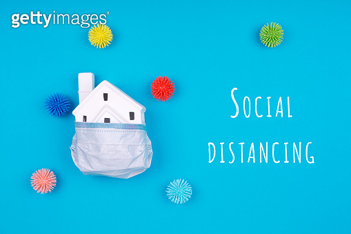 Cute little house covered with medicine mask and plastic balls aka viruses on the blue background with Social Distancing wording. Epidemic, social isolation, coronavirus COVID-19 concept