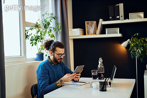 Young attractive caucasian bearded graphic designer sitting at office  and using tablet.