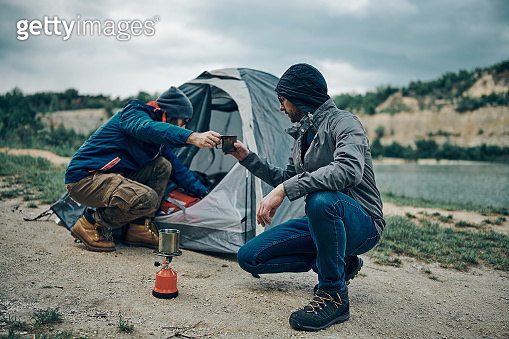 Two best friends crouching next to tent and preparing coffee. Camping trip concept.