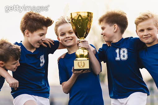 Children winning soccer tournament. Group of happy boys holding golden trophy. School sports team celebrating success. Overjoyed kids in football sports team