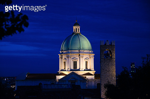 Dome of Santa Maria Assunta New Cathedral, Duomo Nuovo Roman Catholic church and Tower of Palazzo del Broletto palace, night evening view, Brescia city historical centre, Lombardy, Northern Italy
