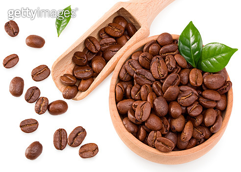 roasted coffee beans with green leaves and wooden spoon in wooden bowl isolated on white background. Clipping path and full depth of field. Top view