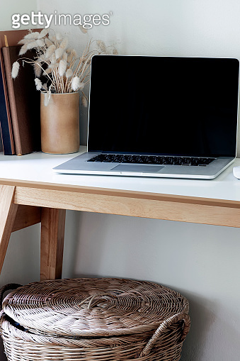 Mockup laptop with blck screen on wooden table, vertical view.