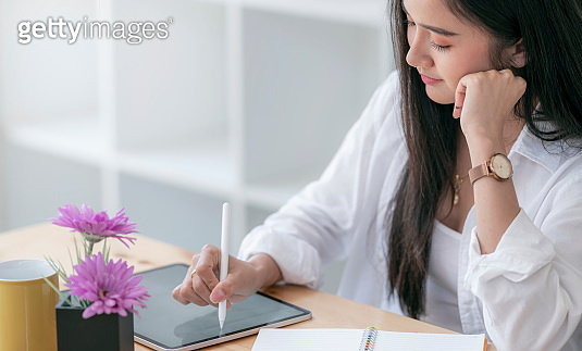 Beautiful asian woman using tablet working at home office.