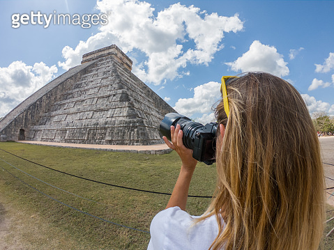Young woman tourist takes a picture of the Mayan ancient temple in Mexico