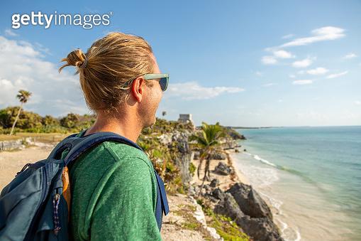 Young man visiting Tulum ruins, Mexico