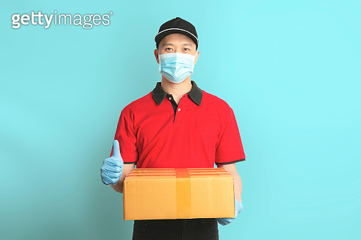 Delivery man employee in red shirt uniform face mask gloves hold empty cardboard box on blue background. Coronavirus virus 2019 concept