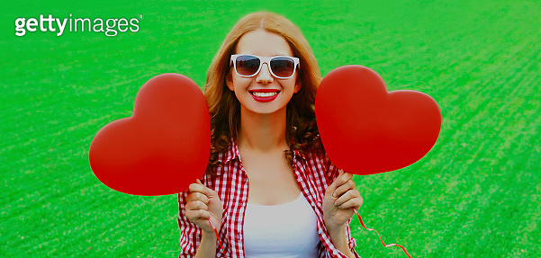 Portrait of happy smiling young woman with red heart shaped air balloon over grass background