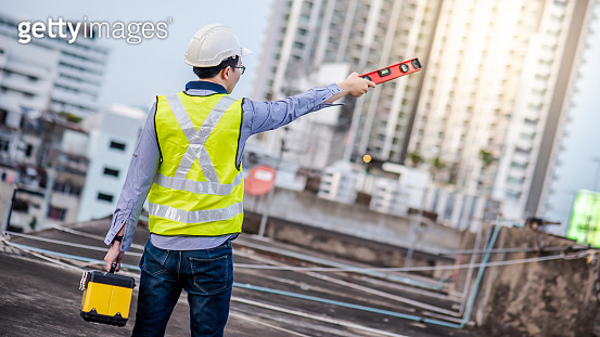 Worker man holding spirit level tool and box
