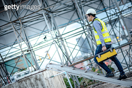 Worker man carrying tool box stepping on aluminium ladder
