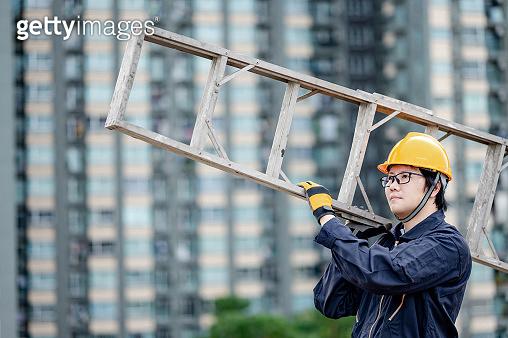 Maintenance worker man carrying aluminium ladder