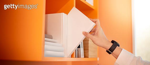 Male hand picking white book on bookshelf
