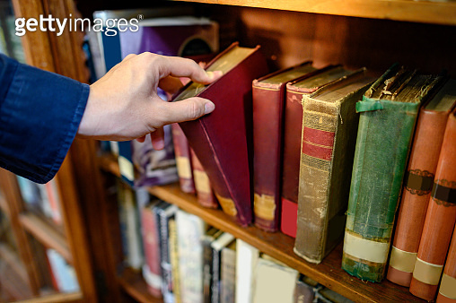 Male hand picking vintage book from bookshelf
