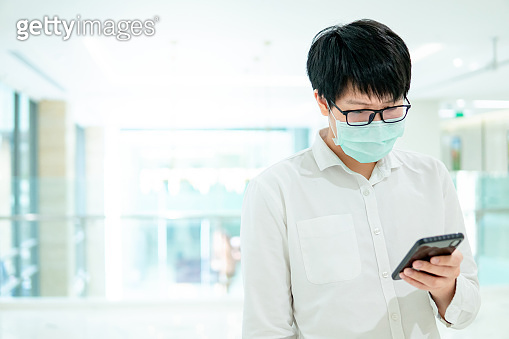 Male patient using smartphone in hospital