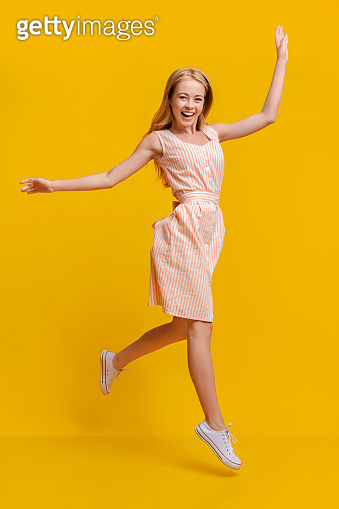 Carefree Youth. Jouful Teen Girl Jumping In Air Over Yellow Background