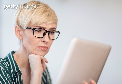 Discontented Businesswoman In Glasses Using Tablet Reading News Sitting Indoor
