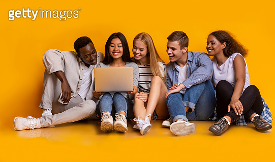 Carefree teenagers sitting on floor and using laptop