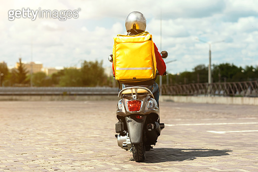 Courier Man Riding Scooter Delivering Food From Restaurants Outdoors, Back-View