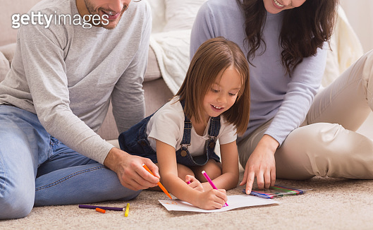 Loving parents teaching their little daughter drawing, sitting together on floor