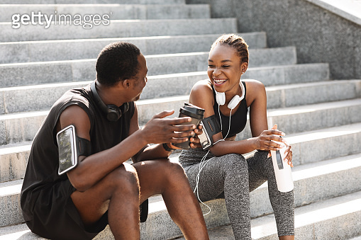 Fit Black Couple Taking Rest After Workout Outdoors, Sitting On Urban Stairs