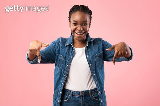 Joyful Black Girl Pointing Fingers Down Posing On Pink Background