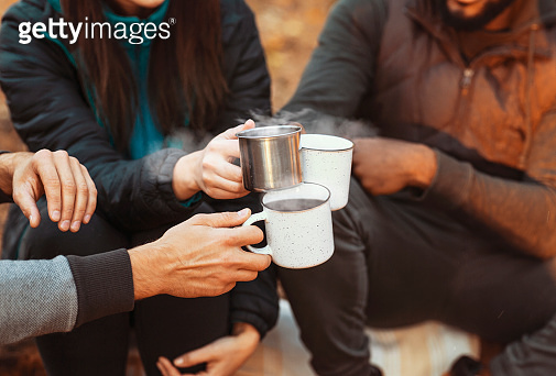 Hands of hikers cheering up with camping cups