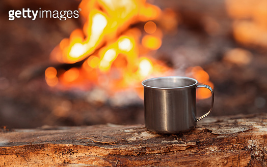Camping cup on wood on fire background