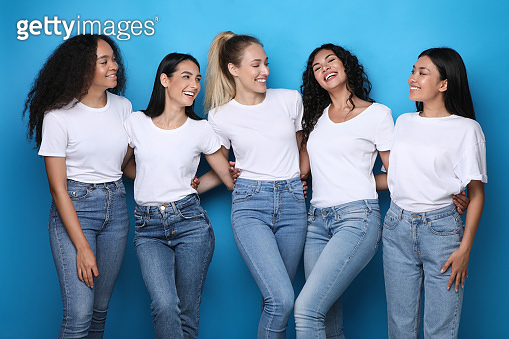 Diverse Young Women Embracing Smiling Each Other Over Blue Background
