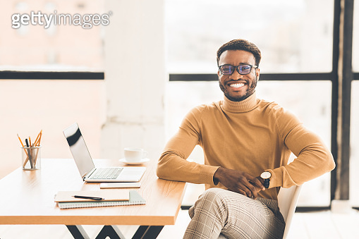 Portrait of happy black manager looking at camera