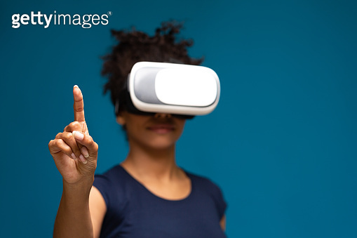 African american lady using VR headset, touching invisible touchscreen