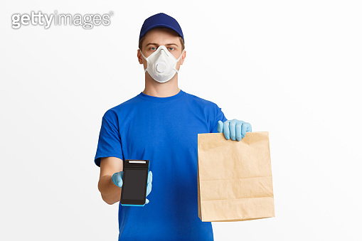 Courier in blue uniform holding package and offers to pay with terminal