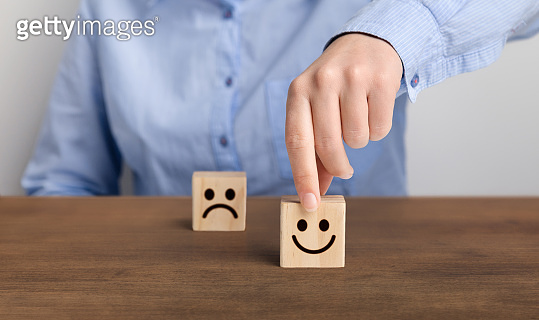 Hand of a businessman chooses a smiley face on wood block cube