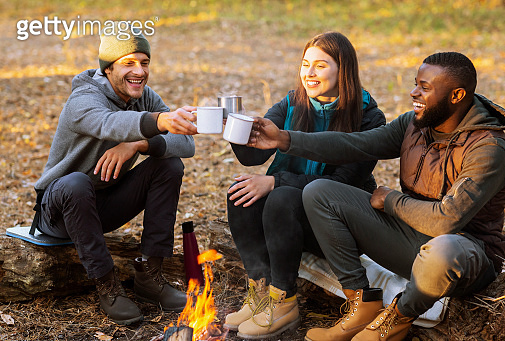 Cheerful hikers toasting for nice camping in sunset lights
