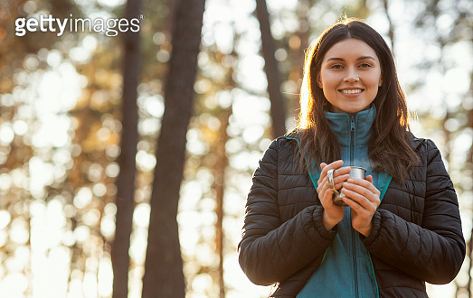 Pretty smiling girl backpacker enjoying her hot tea