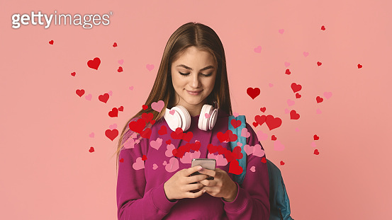 Smiling teenage girl is typing on smartphone, hearts fly out of smartphone