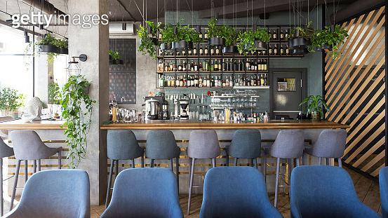 Modern wooden counter zone in empty cafe, green plants