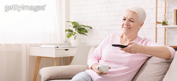 Senior woman watching tv during coronavirus isolation at home