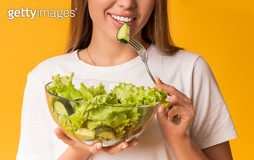Unrecognizable Smiling Woman Eating Fresh Green Vegetable Salad On Yellow Background