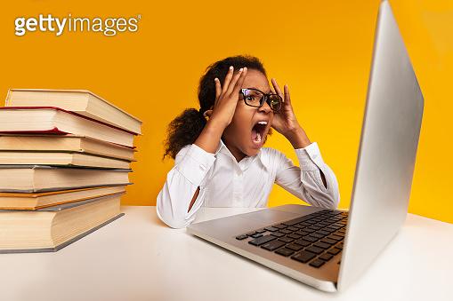 Overworked Schoolgirl Shouting At Laptop Sitting On Yellow Studio Background